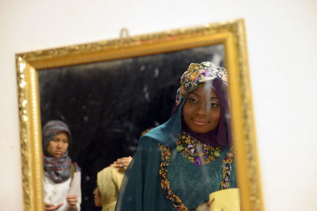 Contestant of the Muslimah World 2013, Obabiyi Aishah Ajibola (C) of Nigeria, is reflected in a mirror checking her make-up while contestants wait for a grand final during the Muslimah World competition in Jakarta on September 18, 2013. (Photo by Adek Berry/AFP Photo)