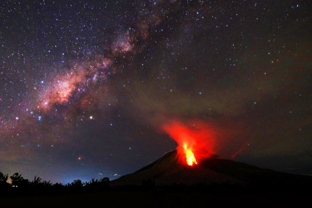 Hot lava flows down the Mount Sinabung volcano in the night in Karo, North Sumatra on July 30, 2017. Sinabung roared back to life in 2010 for the first time in 400 years. After another period of inactivity it erupted once more in 2013, and has remained highly active since. (Photo by Tibta Pangin/AFP Photo)