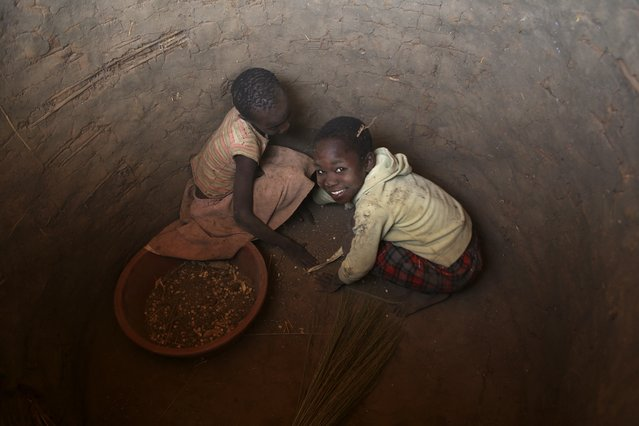 Children clean the interior of a granary in preparation for grain storage in Odek village, north of Uganda capital Kampala February 14, 2015. Odek is the birthplace of Joseph Kony, founder and leader of the rebel group Lord's Resistance Army. (Photo by James Akena/Reuters)