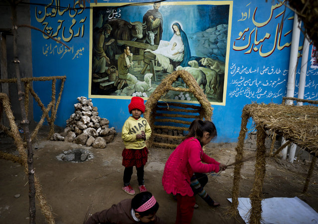 """In this Monday, December 21, 2015 file photo, Pakistani Christian children prepare for Christmas in Islamabad, Pakistan,. Partial translation on the wall reads, """"Merry Christmas and a happy new year"""". (Photo by B.K. Bangash/AP Photo)"""