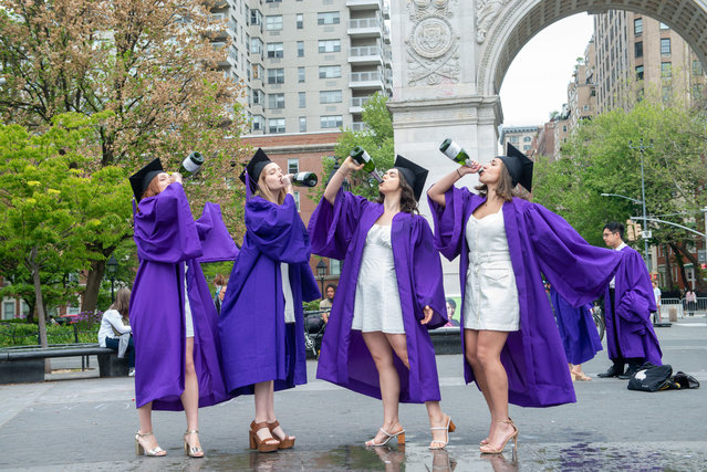 (L-R) Ruby Zinner, 21, Caroline Reinstadler, 22, Marie Kallis, 22, and Julia Bogdanoff, 21, wearing graduation caps and gowns drink champagne while taking graduation photos in Washington Square Park amid the Coronavirus pandemic on May 09, 2021 in New York City. Due to the ongoing coronavirus pandemic NYU's commencement ceremony will be held virtually on May 19th. Students from the 2021 will be invited back for an in person graduation when public health guidelines allow. (Photo by Alexi Rosenfeld/Getty Images)
