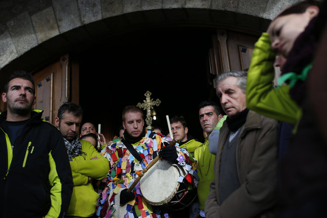 Armando Vicente, 30, third left, wearing his Jarramplas costume stands surrounded by relatives and friends outside a church during the Jarramplas festival in Piornal, Spain, Wednesday, January 20, 2016. (Photo by Francisco Seco/AP Photo)
