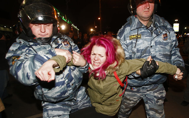 """Police officers detain a protester in Moscow, Russia, Tuesday, October 15, 2013.  Police launched an arrest at subway station """"Prague"""" where nationalists have called to gather citizens. Police stepped up patrols throughout the city on Tuesday to prevent a repeat of 2010 riots, when thousands of nationalists and soccer fans protested the killing of an ethnic Russian during a fight between soccer fans and men from the Caucasus. (Photo by Denis Tyrin/AP Photo)"""