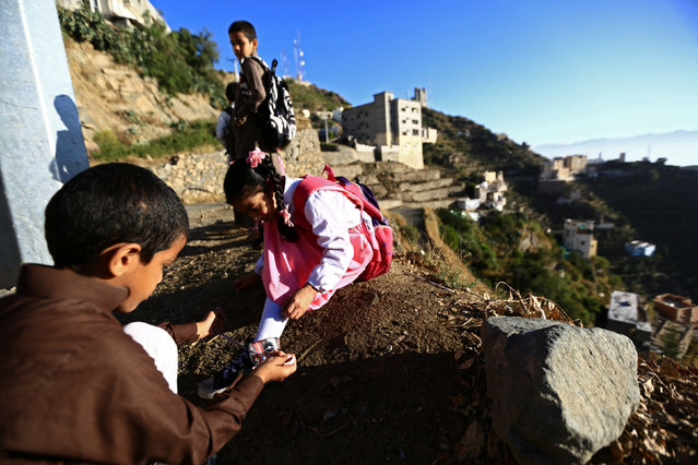 A Saudi boy of al-Fefi family helps his sister as they make their way to their schools through Fifa Mountain, in Jazan, south of Saudi Arabia, December 15, 2016. (Photo by Mohamed Al Hwaity/Reuters)