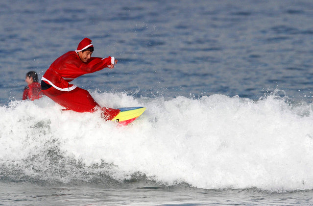 A surfer wearing a Santa Claus costume rides a wave at a beach in Vigo, Spain, 23 December 2016. Dozens of people have welcomed Christmas surfing dressed in Santa suits. (Photo by Salvador Sas/EPA)