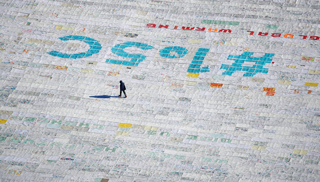 A person walks over 100,000 postcards with messages against climate change, sent by young people from all over the world and stuck together to break the Guinness World Record of the biggest postcard on the Jungfraufirn, the upper part of Europe's longest glacier, the Aletschgletscher, near Jungfraujoch, Switzerland November 16, 2018. (Photo by Arnd Wiegmann/Reuters)