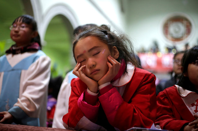 A girl takes a nap during a Christmas eve mass at a Catholic church on the outskirts of Taiyuan, North China's Shanxi province, December 24, 2016. (Photo by Jason Lee/Reuters)