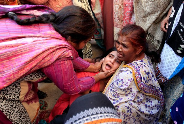 A woman is comfored by others, as she mourns the death of a relative, who died after consuming locally made toxic liquor, in Toba Tek Singh, Pakistan, December 27, 2016. (Photo by Fayyaz Hussain/Reuters)