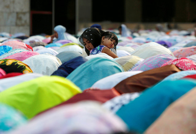 A woman holds her daughter during prayers for the Muslim holiday of Eid al-Adha at Istiqlal mosque in Jakarta, Indonesia, August 22, 2018. (Photo by Willy Kurniawan/Reuters)