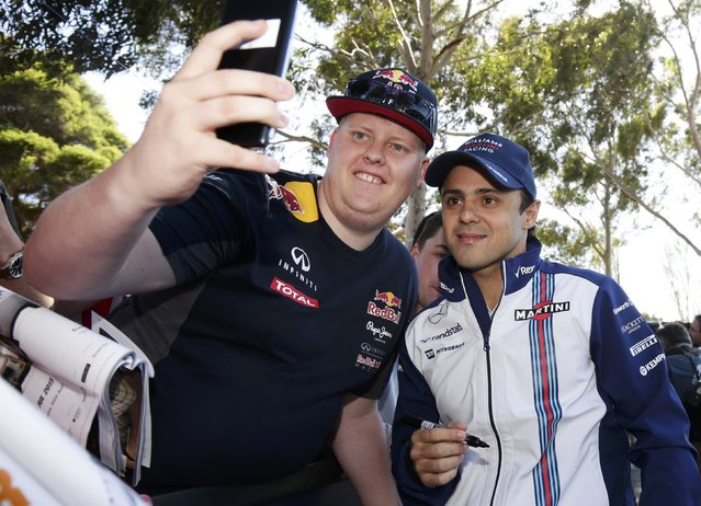 Williams Formula One driver Felipe Massa of Brazil (R) takes a photograph with a fan as he arrives for the first practice session of the Australian F1 Grand Prix at the Albert Park circuit in Melbourne March 13, 2015. (Photo by Mark Dadswell/Reuters)