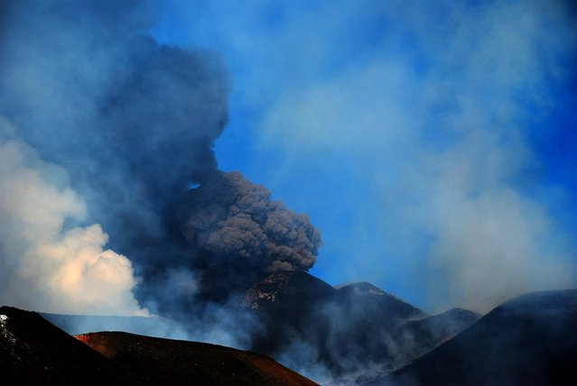 Plumes of smoke are seen on Mount Etna during an eruption October 25, 2013. Etna's eruptions aren't infrequent, although the last major one occurred in 1992. (Photo by Salvatore Allegra/Associated Press)