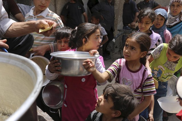 Children carry containers as they queue to receive free meals from a soup kitchen in the besieged town of Deir al-Asafir in the Eastern Ghouta of Damascus May 19, 2015. (Photo by Amer Almohibany/Reuters)