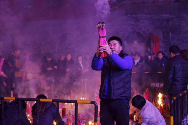 People burn incense as they pray for good fortune on the eve of the Chinese Lunar New Year, at Mingjiao temple in Hefei, Anhui province, February 8, 2016. (Photo by Reuters/Stringer)