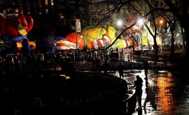 Sightseers throng past giant balloons being prepared for the parade. (Photo by John Moore/Getty Images)