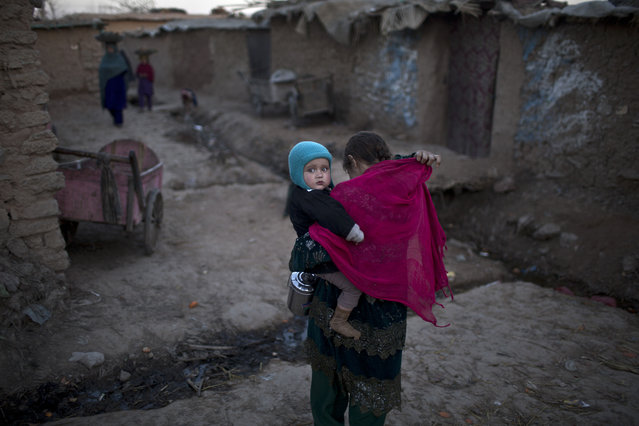 An Afghan refugee girl carrying her younger brother walks back to her mud home in a slum on the outskirts of Islamabad, Pakistan, Saturday, February 14, 2015. (Photo by Muhammed Muheisen/AP Photo)
