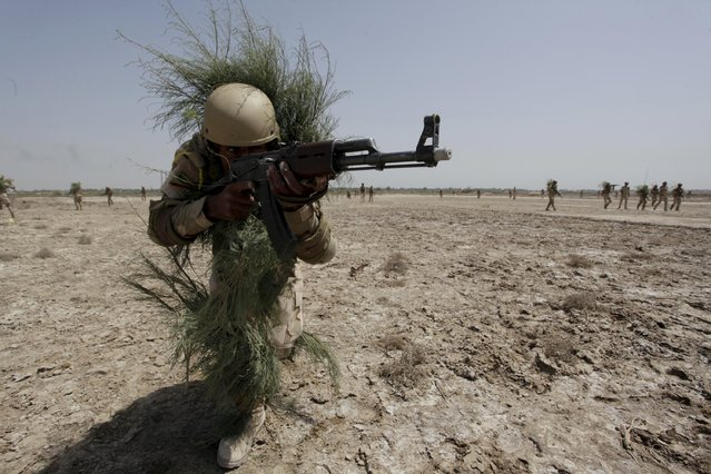 A member from the Iraqi security forces uses bushes as camouflage as part of military training in Jurf al-Sakhar, Iraq April 9, 2015. (Photo by Alaa Al-Marjani/Reuters)