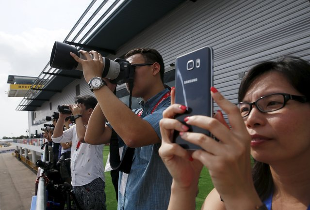 Photographers take photos during a preview of the aerial display of the Singapore Airshow at Changi exhibition center in Singapore February 14, 2016. (Photo by Edgar Su/Reuters)