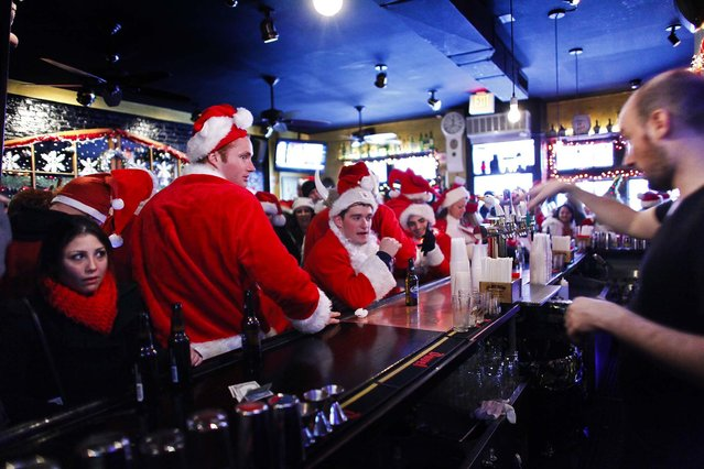 Revelers dressed as Santa Claus drink beer inside a local pub during SantaCon in New York. (Photo by Eduardo Munoz/Reuters)