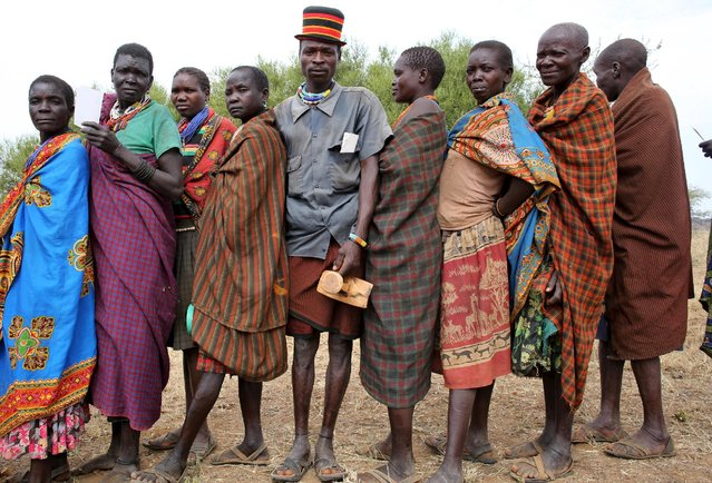 People from Karamojong tribe wait in line to vote in front of a polling station during the presidential elections in a village near town of Kaabong in Karamoja region, Uganda, February 18, 2016. (Photo by Goran Tomasevic/Reuters)