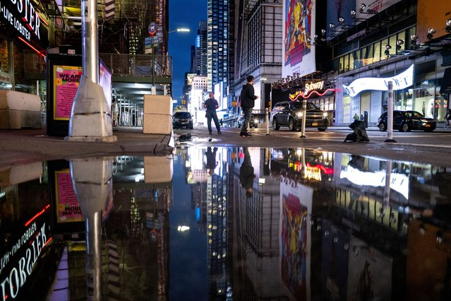The lights of Times Square in New York are reflected in standing water Thursday, September 2, 2021, as Hurricane Ida left behind not just water on city streets but wind damage and severe flooding along the Eastern seaboard. (Photo by Craig Ruttle/AP Photo)