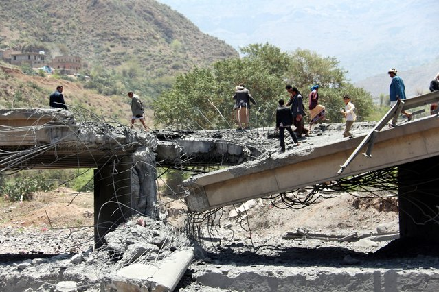 Yemenis stand on a bridge allegedly hit by an airstrike carried out by the Saudi-led coalition near the central city of Ibb, Yemen, 21 April 2015. According to reports, at least 24 people, allegedly all civilians, were killed when an airstrike targeting Houthi militia members hit the bridge, adding to the growing death toll from the past weeks of fighting which some agencies report as reaching 944 with 3487 wounded. (Photo by EPA/Stringer)