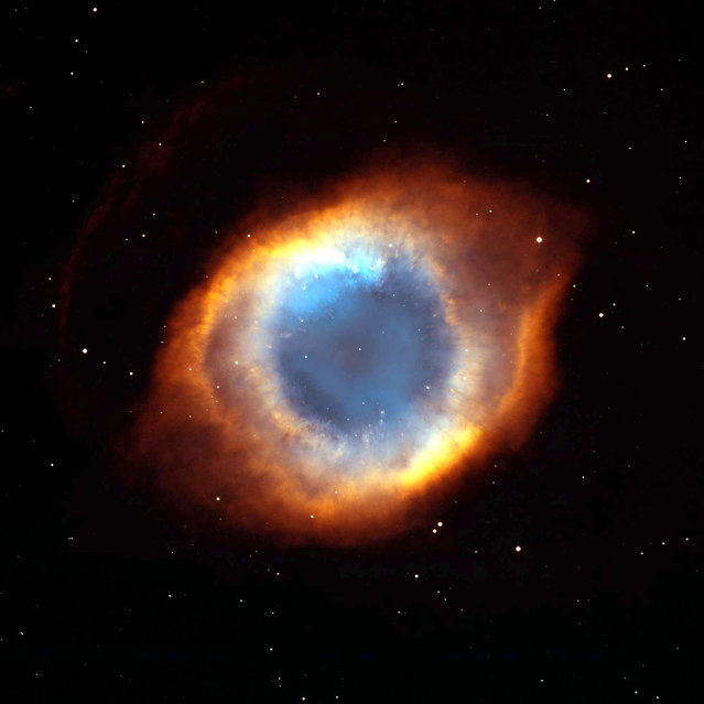 """A coil-shaped Helix Nebula showing a fine web of filamentary """"bicycle-spoke"""" features embedded in the colorful red and blue ring of gas. At 650 light-years away, the Helix is one of the nearest planetary nebulae to Earth. A planetary nebula is the glowing gas around a dying, Sun-like star. (Photo by Reuters/NASA)"""