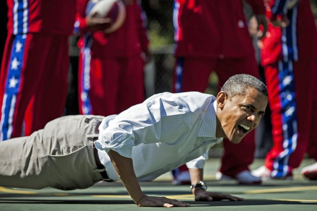 US President Barack Obama does pushups during backetball shooting drills during the annual Easter Egg Roll on the South Lawn of the White House April 9, 2012 in Washington, DC. (Photo by Brendan Smialowski/AFP Photo)
