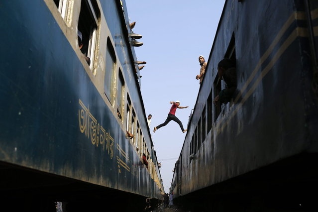 A man jumps from the top of one overcrowded train to another as thousands of Bangladeshi Muslims try to return home after attending three-day Islamic Congregation on the banks of the River Turag in Tongi, 20 kilometers (13 miles) north of the capital Dhaka, Bangladesh, Sunday, January 26, 2014. (Photo by A. M. Ahad/AP Photo)