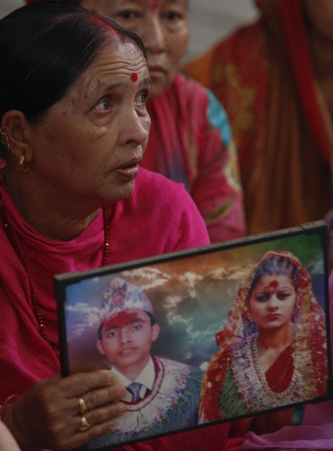 Indian woman Padma holds a photograph showing her son Bharat and daughter in law Partima with whom she has not been able to establish contact after Saturday's earthquake in Nepal, during a prayer ceremony for the earthquake affected at a Hindu temple in Jammu, India, Monday, April 27, 2015. (Photo by Channi Anand/AP Photo)
