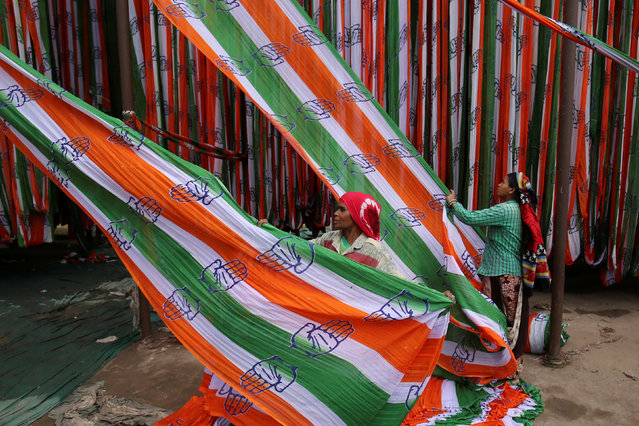 A worker pulls a roll of flags of India's main opposition Congress party kept for drying at a flag manufacturing factory, ahead of the 2019 general elections, in Ahmedabad, India, March 13, 2019. (Photo by Amit Dave/Reuters)