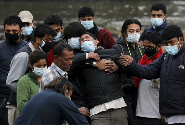 Family members cry over the body of one of their family member, who died in Saturday's earthquake, during the cremation along a river in Kathmandu, Nepal April 28, 2015. (Photo by Adnan Abidi/Reuters)