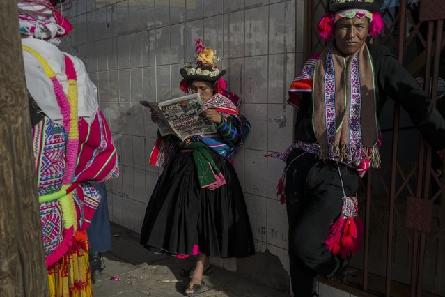 In this January 29, 2017 photo, a dancer reads a newspaper while waiting to perform during Virgin of Candelaria celebrations in Puno, Peru. As many as 40,000 villagers are expected to gather for the annual festival and show their respect for the patron saint of the communities along the shores of Lake Titicaca. (Photo by Rodrigo Abd/AP Photo)
