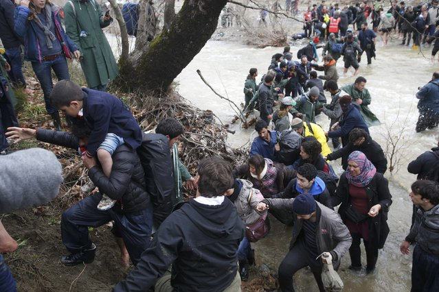 Migrants wade across a river near the Greek-Macedonian border, west of the the village of Idomeni, Greece, March 14, 2016. (Photo by Stoyan Nenov/Reuters)