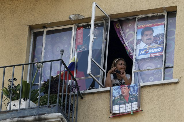 A supporter of Venezuela's President Nicolas Maduro attends a rally from her window to celebrate May Day in Caracas May 1, 2015. (Photo by Jorge Silva/Reuters)