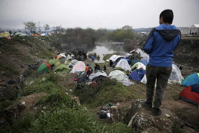 A migrant (R) gazes upon tents at a makeshift camp for refugees and migrants at the Greek-Macedonian border, near the village of Idomeni, Greece March 16, 2016. (Photo by Alkis Konstantinidis/Reuters)