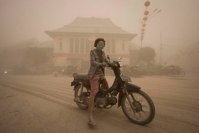 A women rides a motor bike on a street covered with volcanic ash from an eruption of Mount Kelud, in Solo, Indonesia, Friday, February 14, 2014. A major volcanic eruption in Indonesia blasted clouds of ash and debris 18 kilometers (12 miles) into the air on Friday, forcing authorities to close six airports, cancel flights elsewhere in Southeast Asia and evacuate more than 100,000 people from the mountain. (Photo by Hafidz Novalsyah/AP Photo)