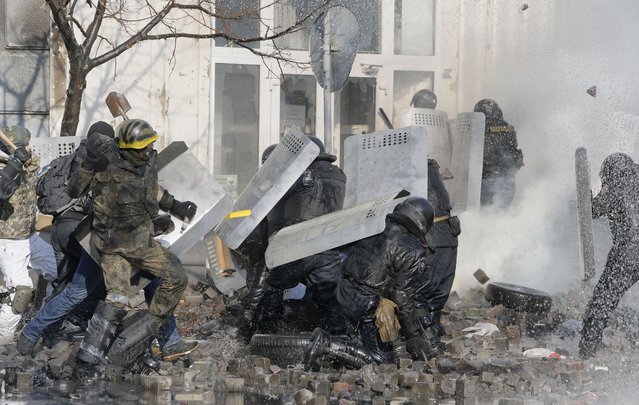 Anti-government protesters clash with riot police outside Ukraine's parliament in Kiev, Ukraine, Tuesday, February 18, 2014. (Photo by Efrem Lukatsky/AP Photo)