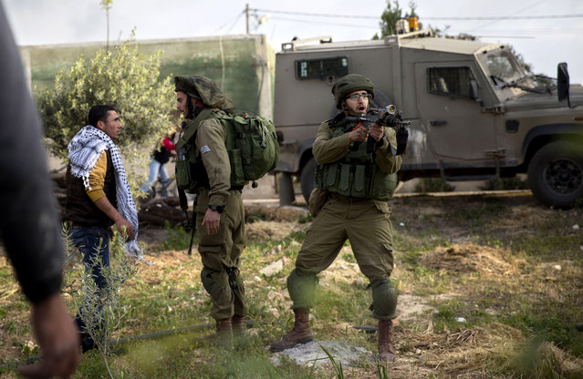 Israeli soldiers scuffle with a Palestinian man near a house that was torched in the Palestinian village of Duma near the West Bank city of Nablus, Sunday, March 20, 2016. A Palestinian home near the site of an arson attack that killed three Palestinians last year caught fire early Sunday, Israeli and Palestinian officials said, with immediate suspicion falling on Jewish extremists. (Photo by Majdi Mohammed/AP Photo)