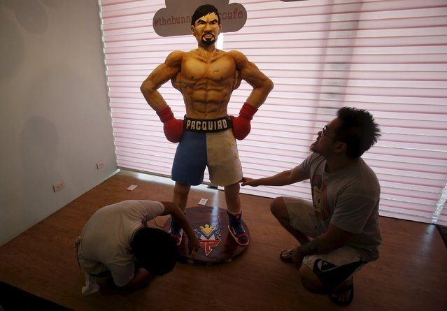Baker Zach Yonson (R) and an assistant put finishing touches on a life-size 70-kg chocolate cake of local boxing icon Manny Pacquiao at a restaurant in Manila, Philippines May 2, 2015. From air-conditioned corporate boardrooms to steamy public gymnasiums, Filipinos are counting down the hours to Pacquiao's fight with undefeated American Floyd Mayweather Jr. in Las Vegas. (Photo by Erik De Castro/Reuters)