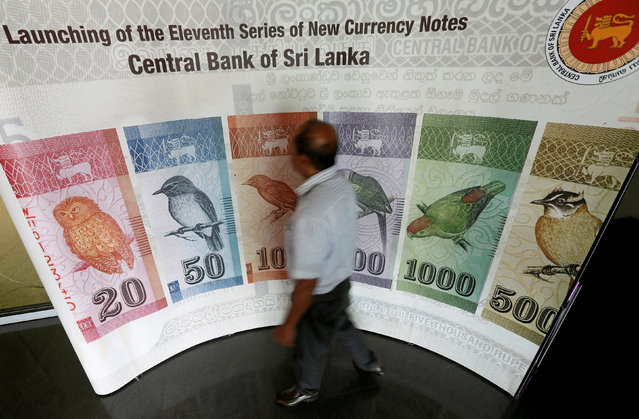 A man walks past a board of Sri Lankan currency presented by Central Bank in Colombo, Sri Lanka February 7, 2017. (Photo by Dinuka Liyanawatte/Reuters)