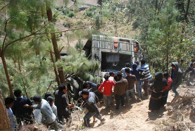 Residents stand next to the wreckage of a bus, which plunged down a ravine, in Nahuala, Guatemala, March 28, 2016. (Photo by Reuters/Stringer)