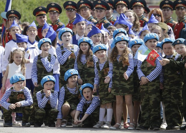 Children and honour guards watch a performance during the so-called parade of children's troops in Rostov-on-Don, southern Russia, May 14, 2015. About 500 children aged from 4 to 10. (Photo by Eduard Korniyenko/Reuters)