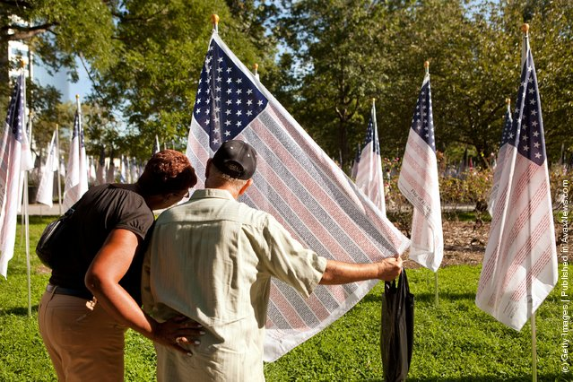 Rivera Leo, from New York, reads names on a flag in the Rembrance Field of Honor, an installation of flags in Battery Park, in memory of the victims of the terrorist attacks on September 11, 2001