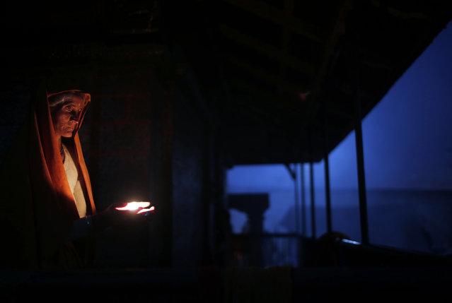 A Hindu holy woman lights an oil lamp during Shivaratri festival in Kathmandu, Nepal, Friday, February 24, 2017. Shivaratri, or the night of Shiva, is dedicated to the worship of Lord Shiva, the Hindu god of death and destruction. (Photo by Niranjan Shrestha/AP Photo)