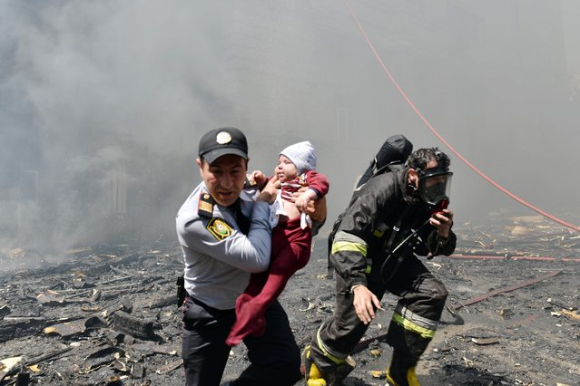 A police officer and a fire fighter help child victim of an apartment building fire in Baku, Azerbaijan, Tuesday, May 19, 2015. Azerbaijani officials say 16 people have died and more than 50 have been injured in a fire at an apartment building in Baku, the capital. The massive fire quickly engulfed 16-story apartment building Tuesday and took hours to contain. Azerbaijan's chief prosecutor, Zakir Garalov. (Photo by Orxan Azim/AP Photo)