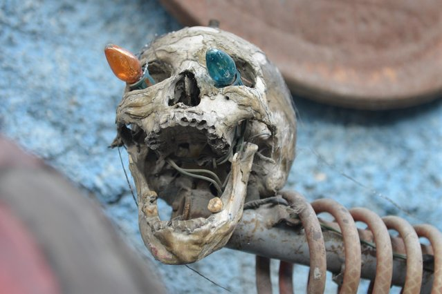 In this April 6, 2016 photo, a sculpture made out of industrial junk and topped with a human skull with Christmas lights sticking out of its eye sockets stands at an open-air museum and art workshop off a trash-strewn street cutting through some of the poorest neighborhoods in Port-au-Prince, Haiti. The site is in the yard of a founding member of a loose collective of Haitian artists called Atis Rezistans who have become celebrated in the international art world by creating sculptures out of scrapped car parts, old wood, discarded toys and even human skulls found scattered outside crumbling mausoleums. (Photo by David McFadden/AP Photo)
