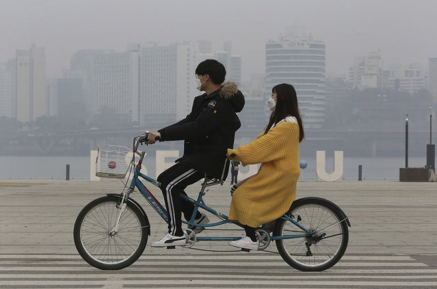 A couple wearing masks ride a bicycle as the cityscape is covered with a thick haze of fine dust particles in Seoul, South Korea, Tuesday, March 5, 2019. South Korean Environment Ministry issued emergency fine dust reduction measures on Tuesday. (Photo by Ahn Young-joon/AP Photo)
