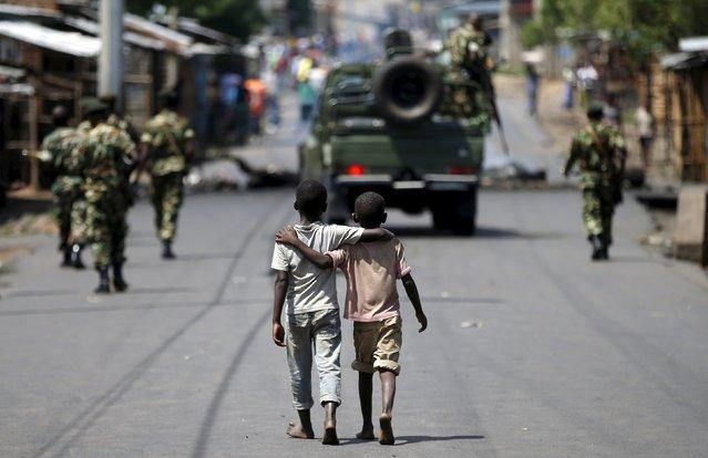 Boys walk behind patrolling soldiers in Bujumbura, Burundi, May 15, 2015. (Photo by Goran Tomasevic/Reuters)
