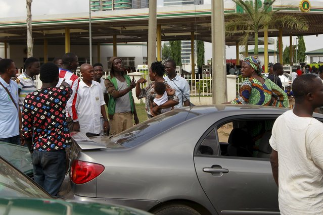 A woman holding her baby argues with a man outside the NNPC mega petrol station in Abuja, Nigeria May 25, 2015. (Photo by Afolabi Sotunde/Reuters)