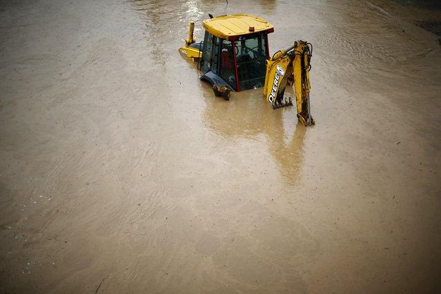 A bulldozer partially covered with water is seen on a flooded street in Santiago, April 17, 2016. (Photo by Ivan Alvarado/Reuters)